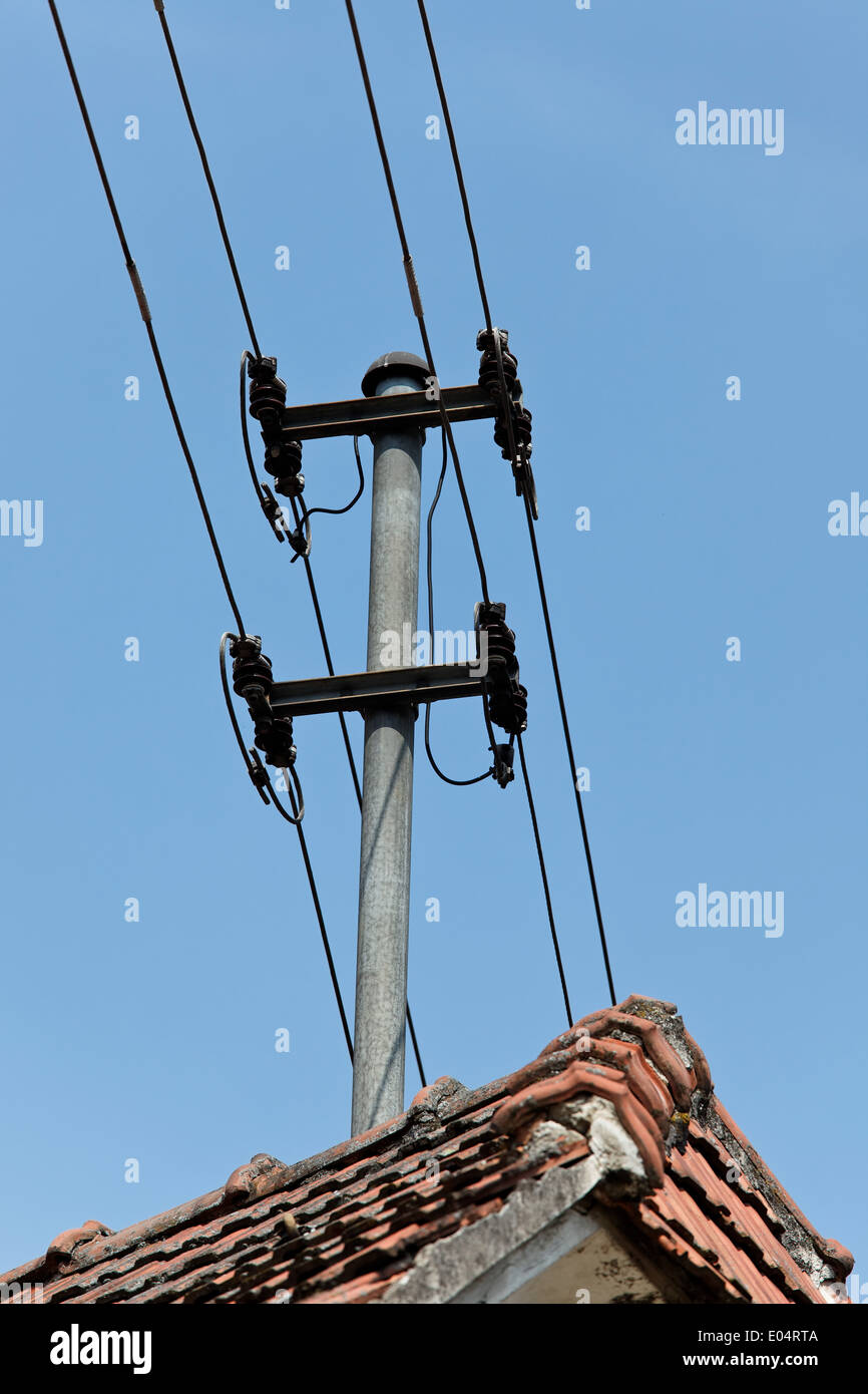 Stream and phone cable bearer on a house roof Mounts, Strom und Telefonkabel Traeger auf einem Hausdach montiert - Stock Image