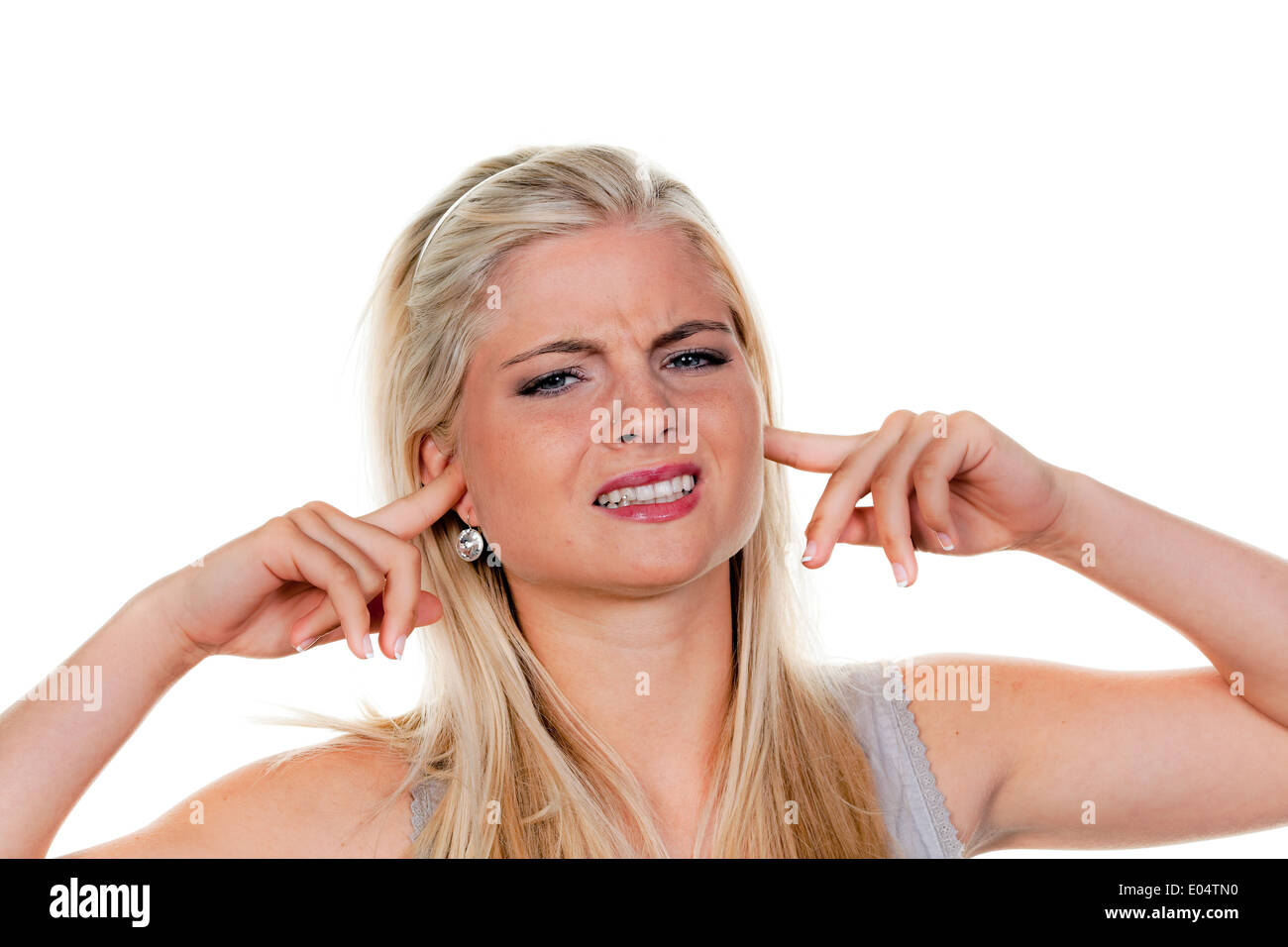 Young woman suffers from noise pollution, keeps closed to herself the ears., Junge Frau leidet unter Laermbelaestigung, haelt si - Stock Image
