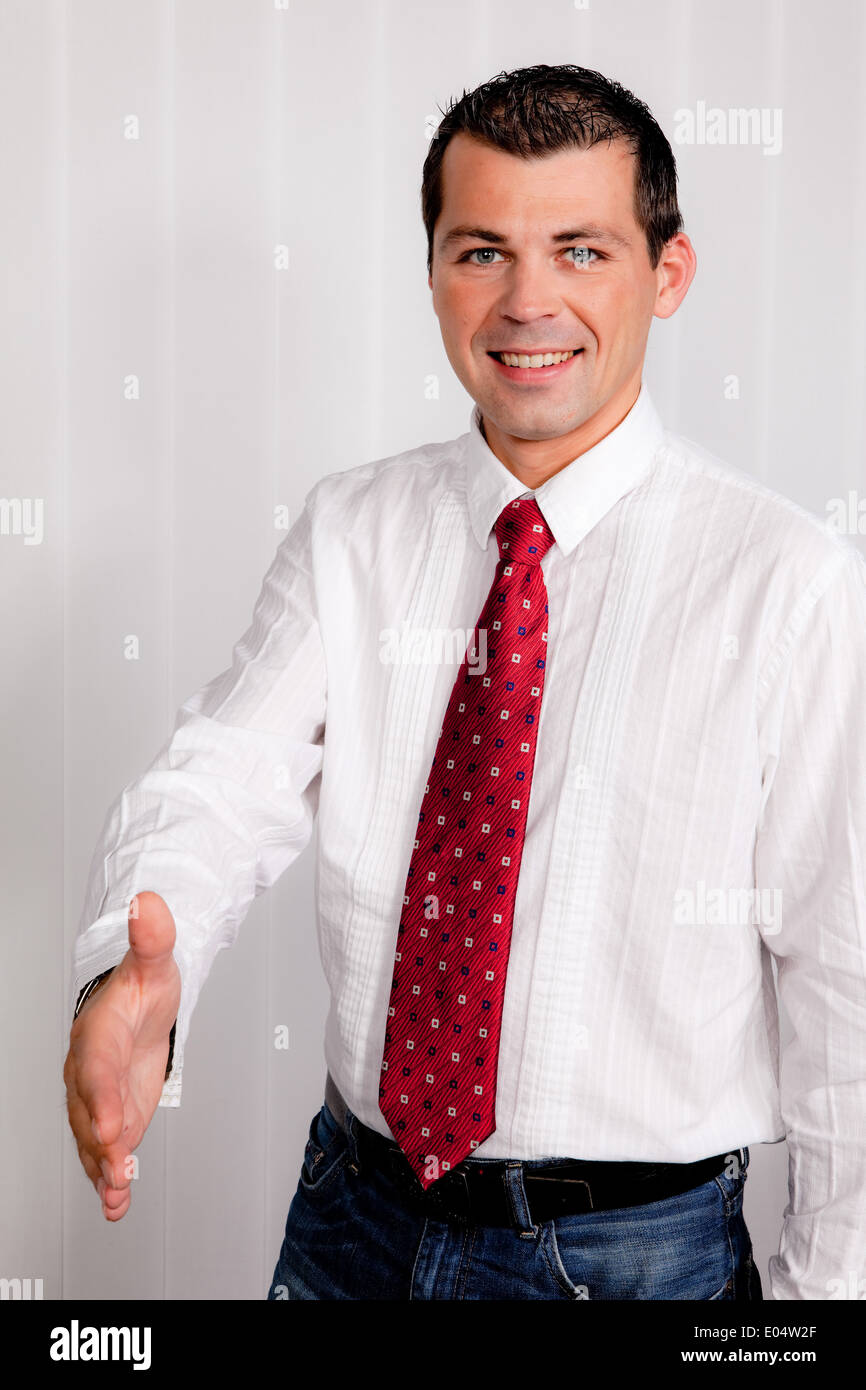 Young man in the office giving handshake - Stock Image