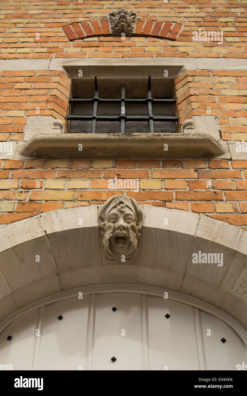 Carved stone gargoyle on a house in Bruges, Belgium Stock Photo
