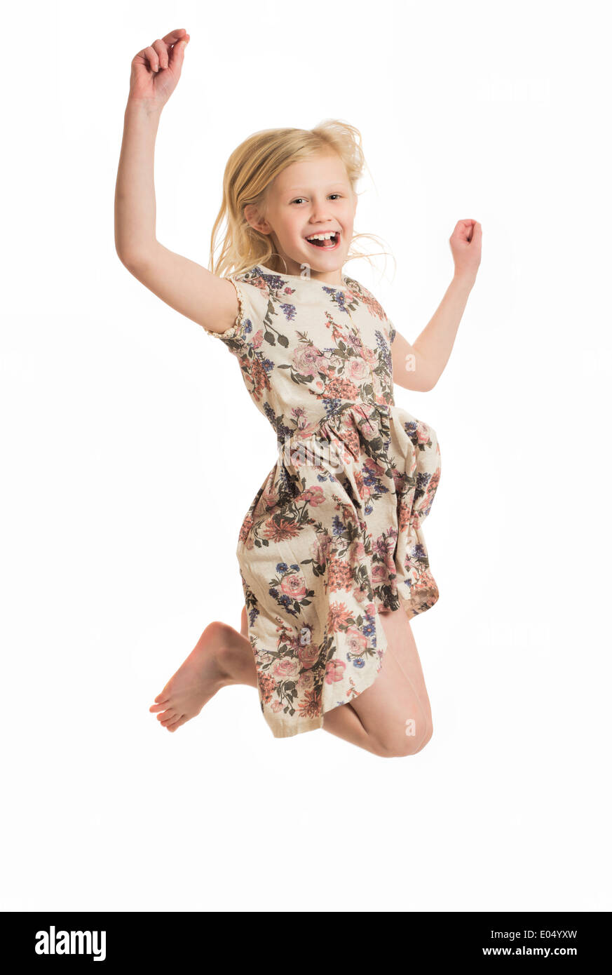 Young happy girl jumping isolated on a white background - Stock Image