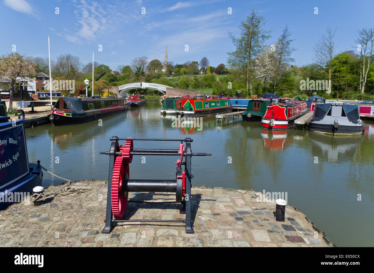 Braunston Marina, UK; old winching gear in the foreground, moored narrow boats in the background - Stock Image