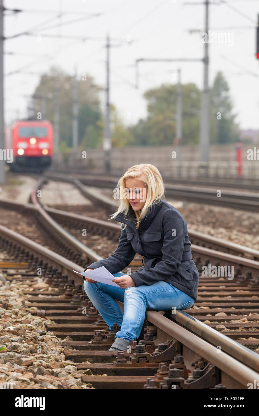 A young woman with suicide thoughts sits on a rail. If farewell letter holds in the hand and thinks about her suicide., Stock Photo