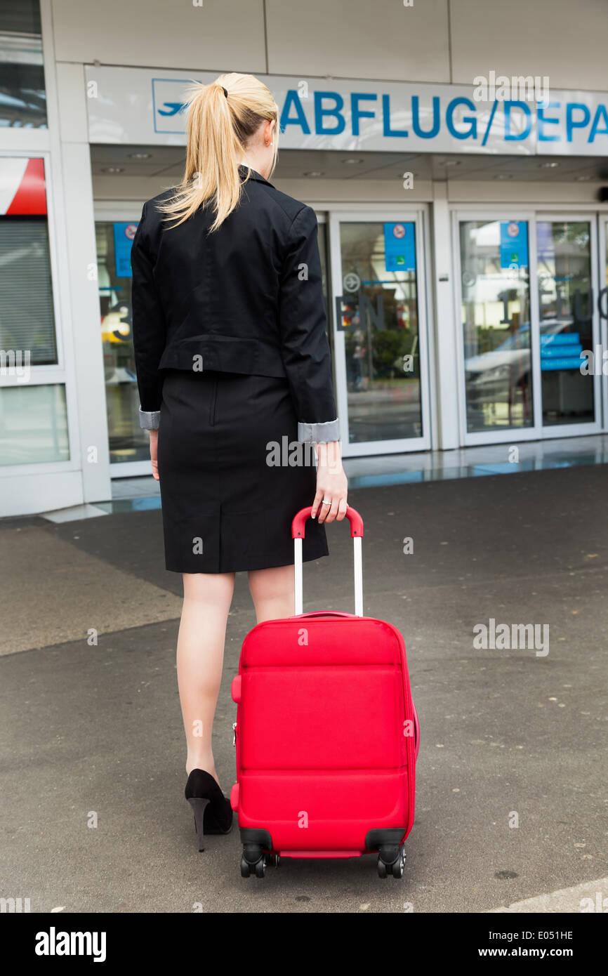 A young businesswoman with suitcase on an airport., Eine junge Geschaeftsfrau mit Koffer auf einem Flughafen. Stock Photo