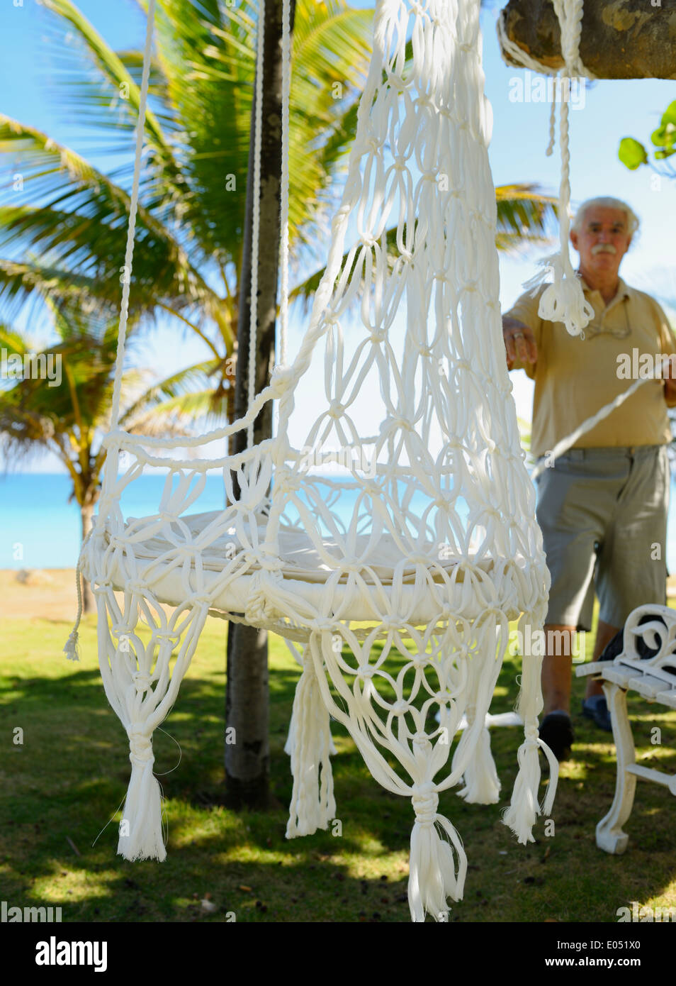 Cuban craftsman tying new white hammocks by the sea shore in Varadero Cuba vacation resort - Stock Image
