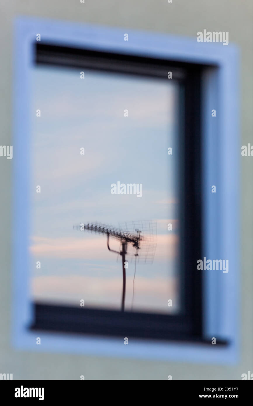 An aerial for a television set is reflected in the window of a dwelling house, Eine Antenne fuer ein Fernsehgeraet Stock Photo