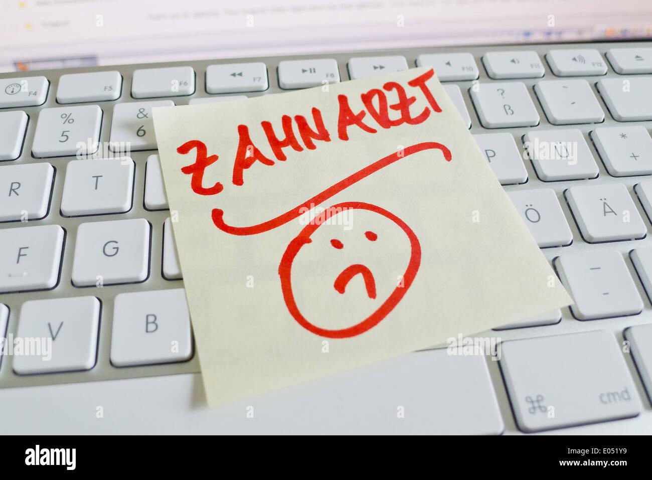 A note slip of paper lies on the keyboard of a computer in memory: Dentist, Ein Notizzettel liegt auf der Tastatur Stock Photo