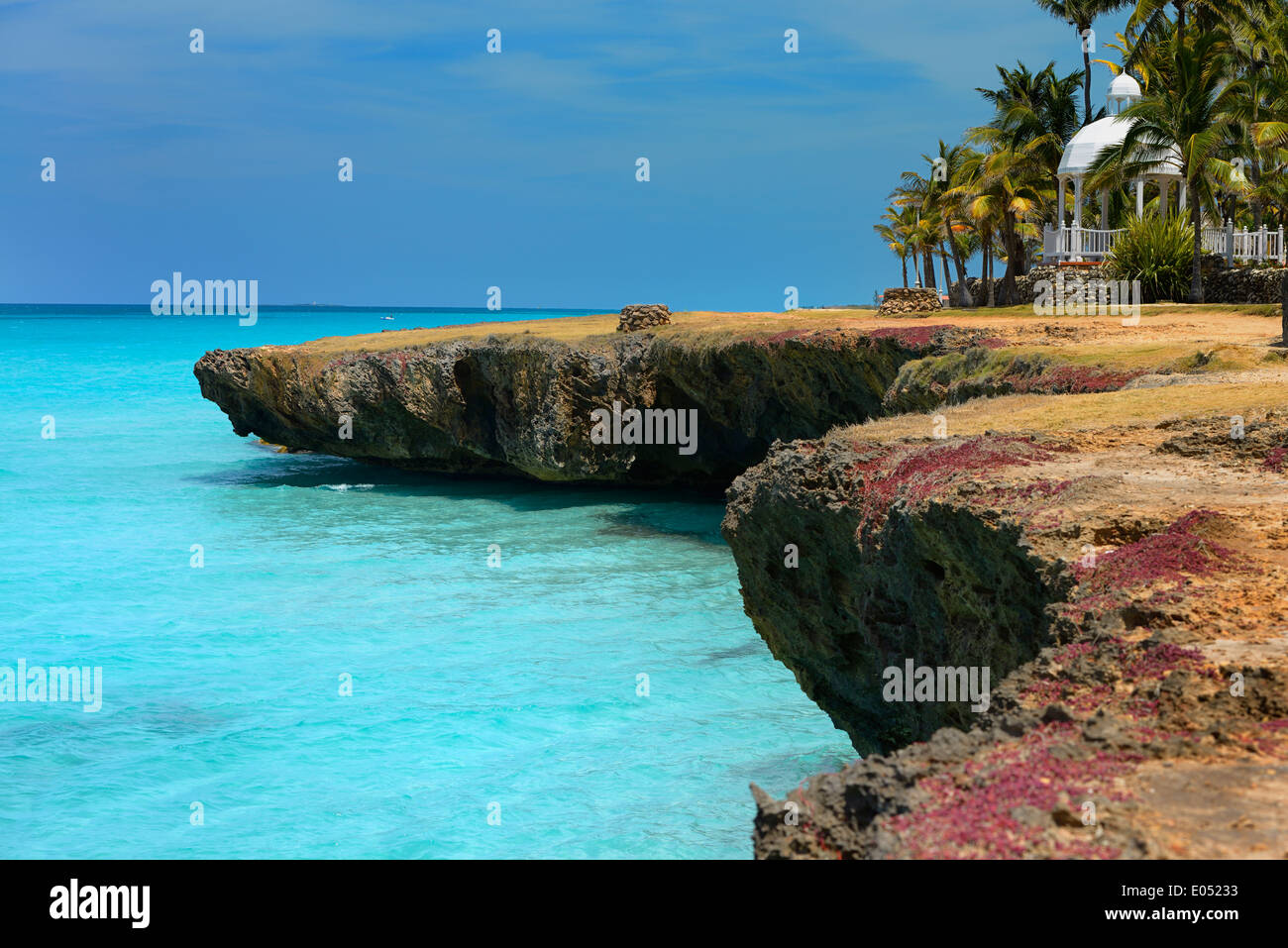 Lava rock shore with blow hole wells Palm trees and gazebo at Varadero Cuba resort with turquoise ocean - Stock Image