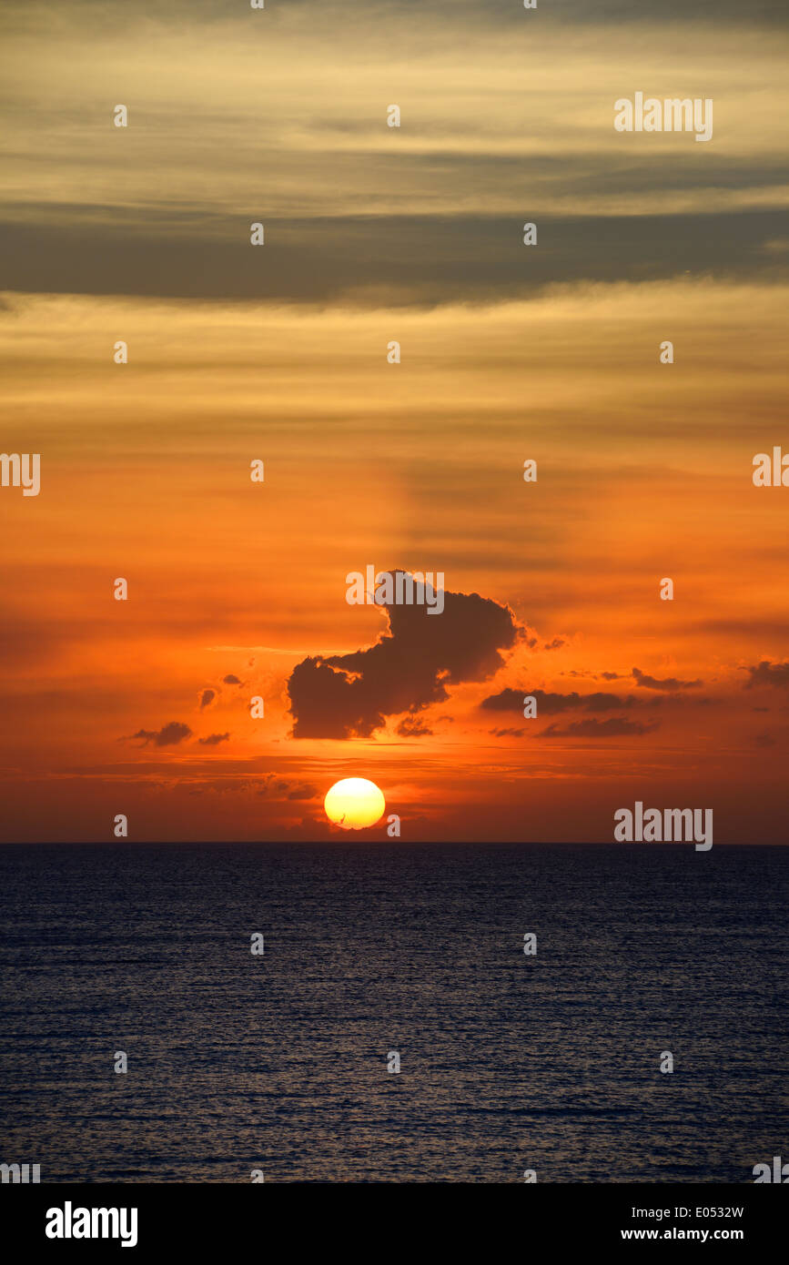 Orange ball sunset near horizon with clouds and sun rays over the Atlantic Ocean in Varadero Cuba - Stock Image