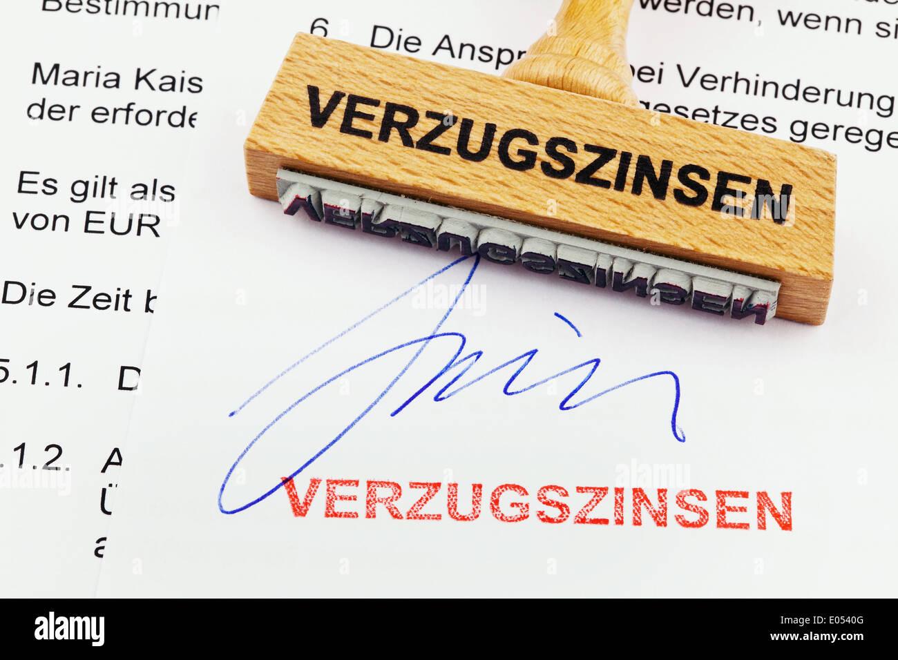 A stamp of wood lies on a document. German label: Interests on arrears, Ein Stempel aus Holz liegt auf einem Dokument. Stock Photo