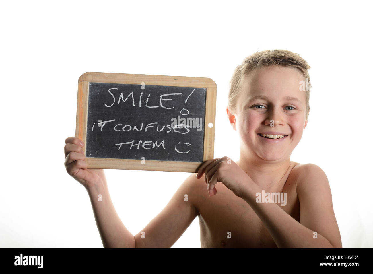 Stock photo of a yong teenager holding a chalk baord messaying saying smile it confuses them - Stock Image