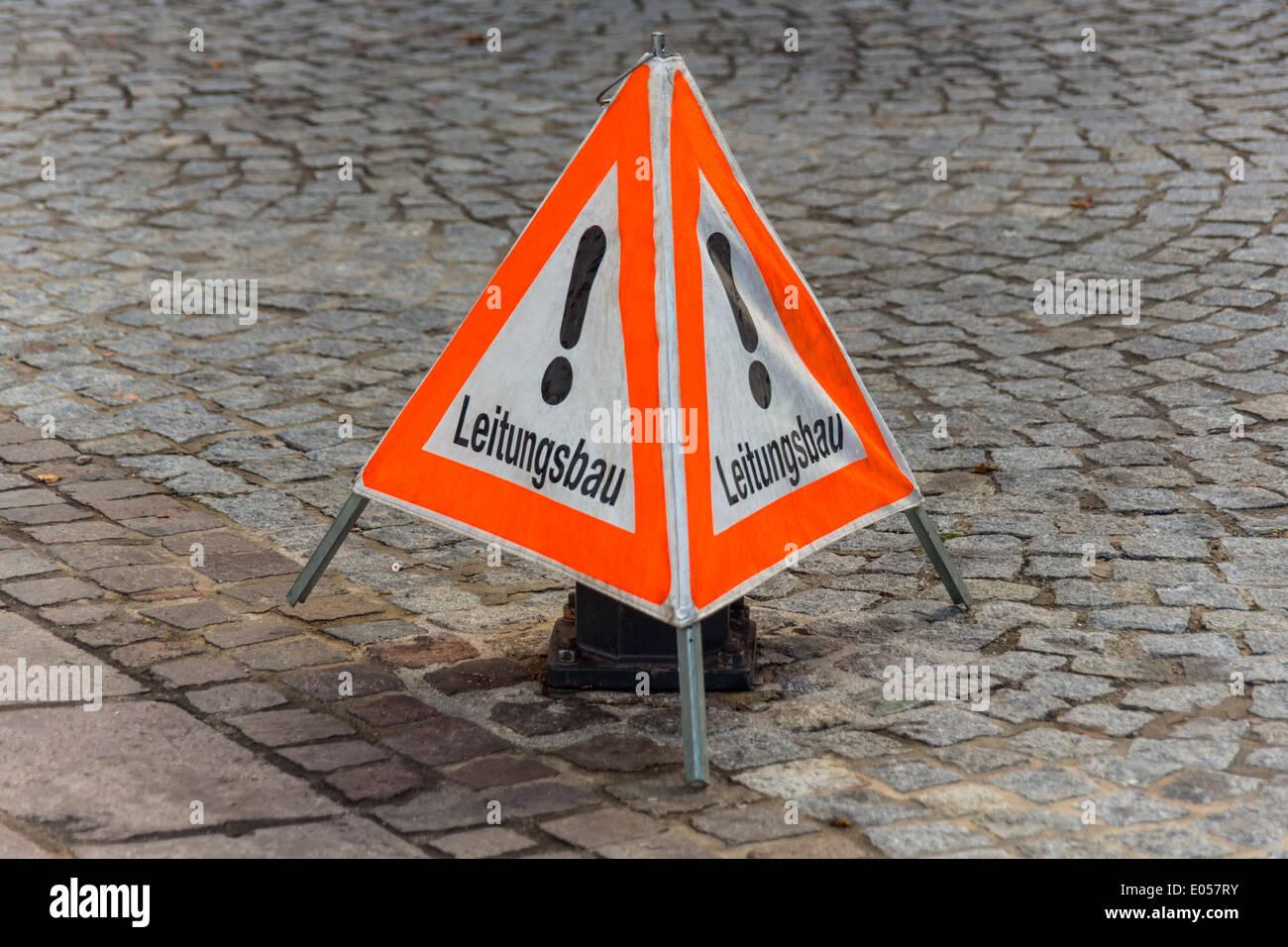 The traffic sign line construction secures a building site, Das Verkehrszeichen Leitungsbau sichert eine Baustelle Stock Photo