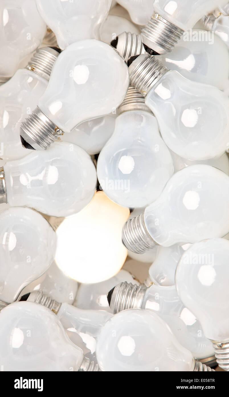 Many light bulbs lie side by side. One shines of it, Viele Gluehbirnen liegen nebeneinander. Eine davon leuchtet - Stock Image