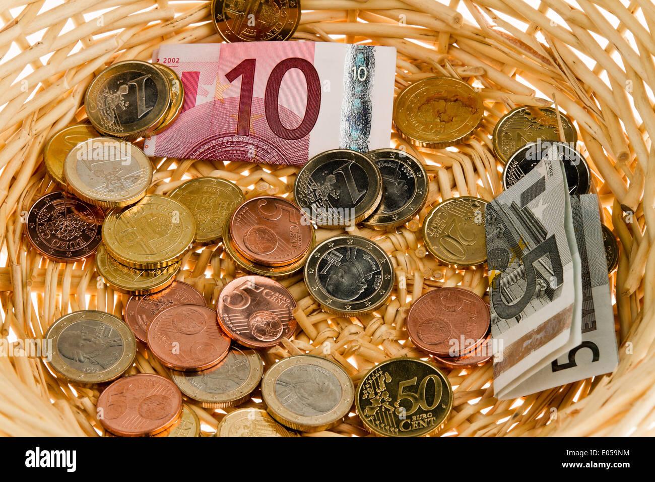 A donation basket for collection. Money donation with euro, Ein Spendenkorb fuer Sammlung. Geld Spende mit Euro - Stock Image