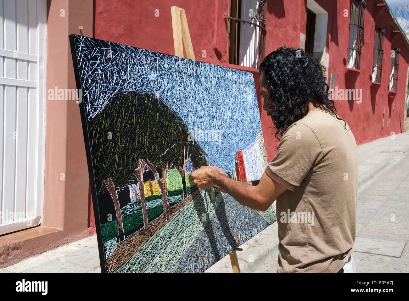 Artist creating needlework picture Oaxaca City Mexico - Stock Image