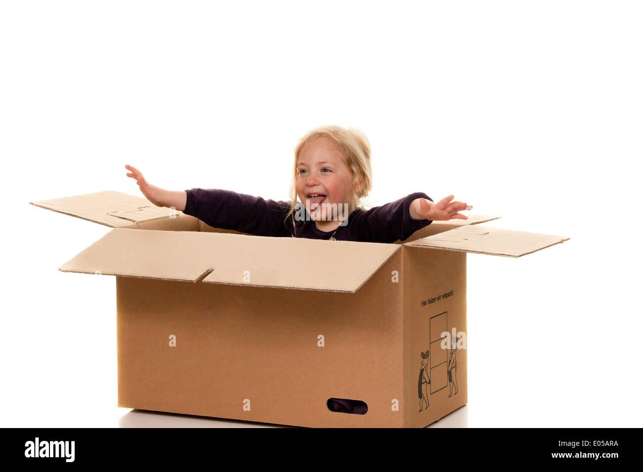 Child in move cardboard. Lies with the move in box., Kind in Umzugskarton. Liegt beim Umzug in Schachtel. Stock Photo