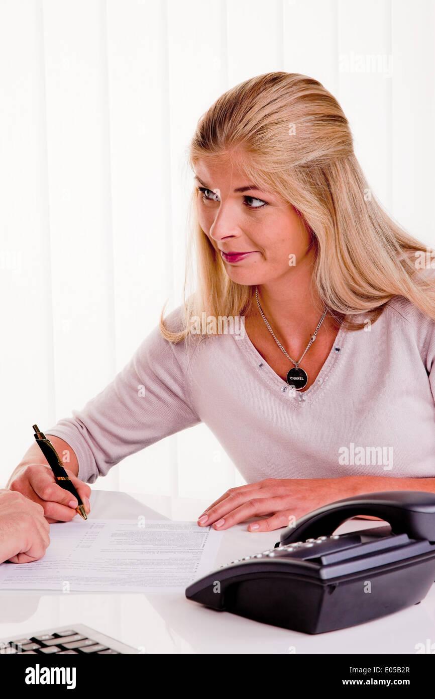 Young woman signs a contract in an office, Junge Frau unterschreibt einen Vertrag in einem Buero Stock Photo