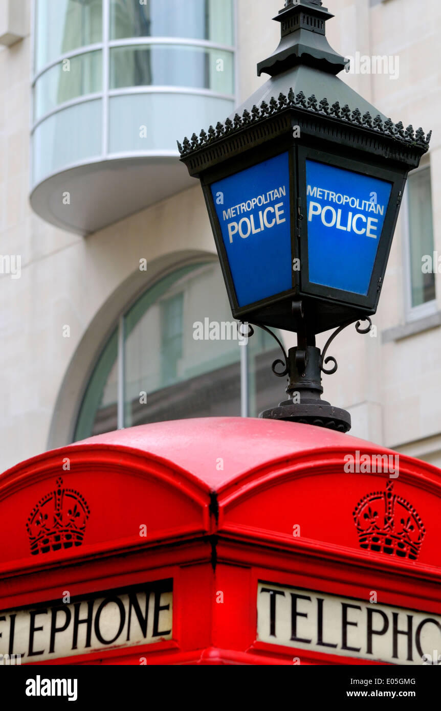 London, England, UK. Traditional red telephone box and blue Metropolitan Police lamp in Agar Street, by Zimbabwe House - Stock Image