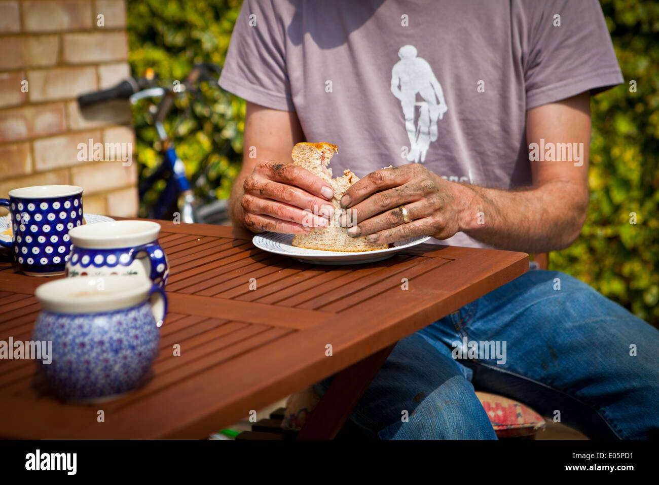 Man eating sandwich with dirty hands - Stock Image