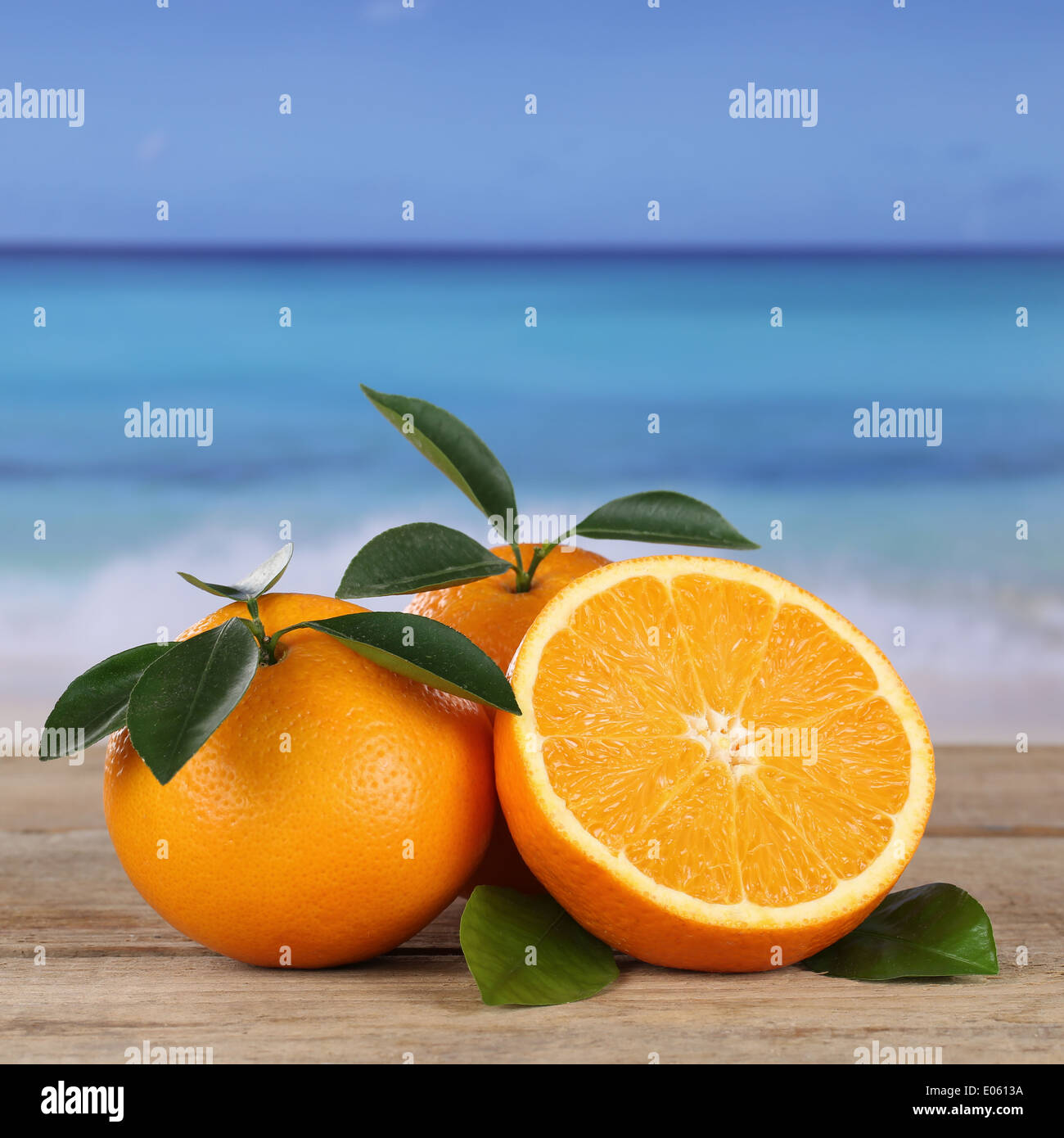 Fresh oranges fruits on the beach and sea with copyspace - Stock Image