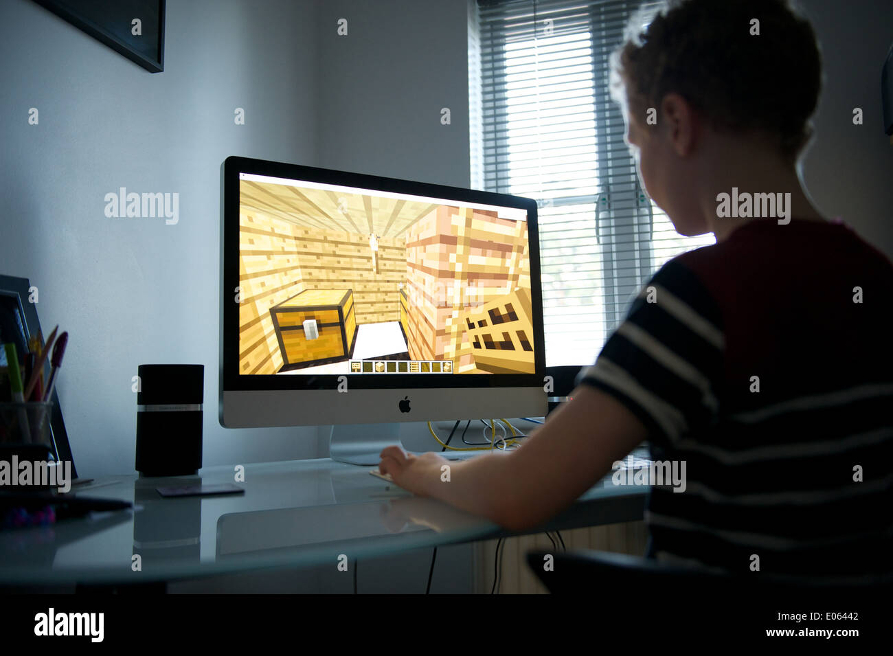 A young nine year old boy playing minecraft on a desktop mac PC - Stock Image