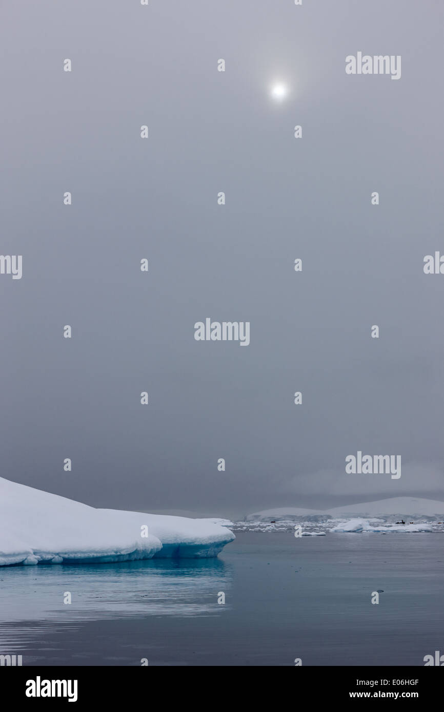 sun breaking through mist and cloud over snow covered ice shelf falling into the sea at Fournier Bay Antarctica - Stock Image