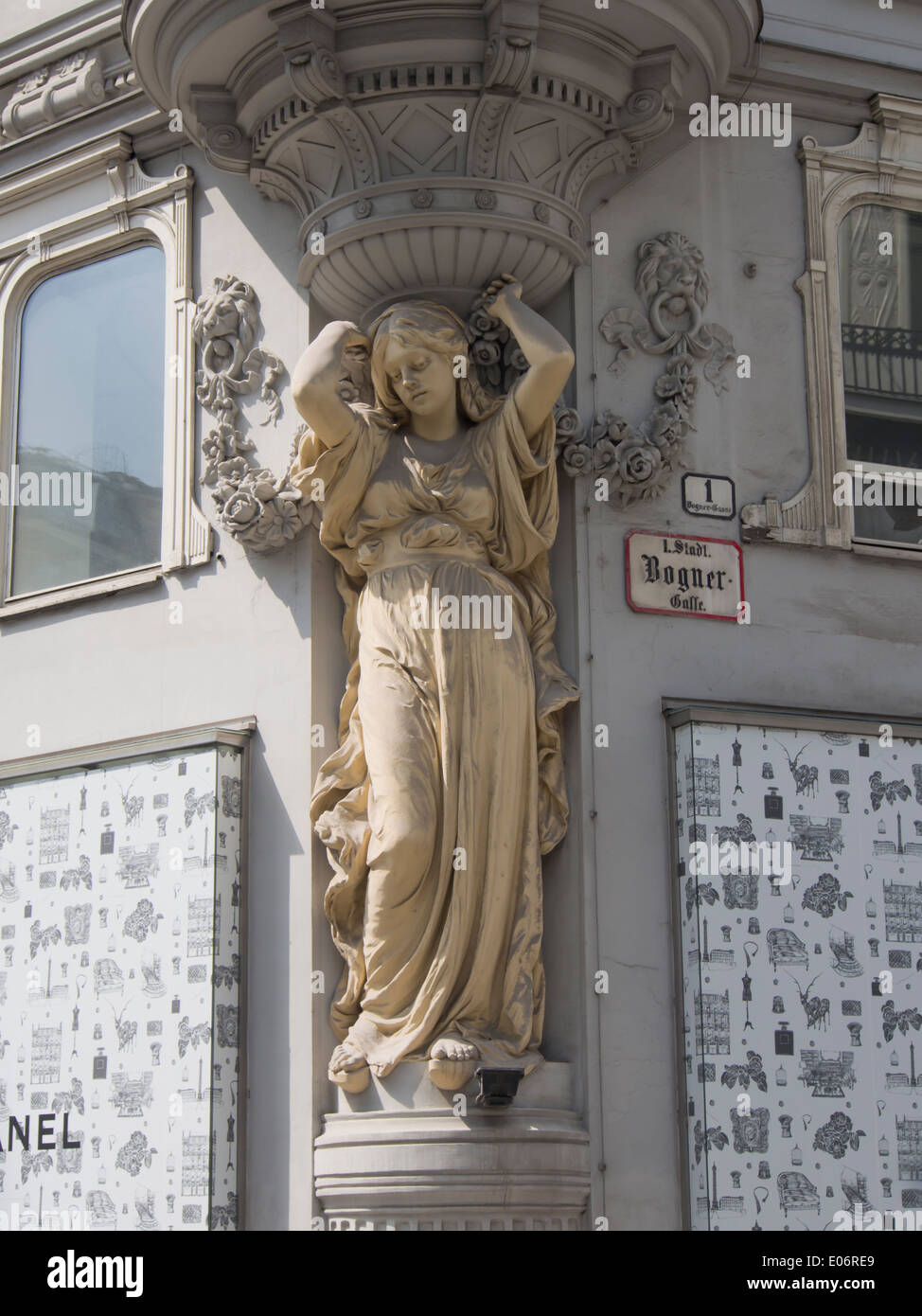 Plaster statue of woman holding up the building, adorning a street corner in the shopping district of Vienna Austria - Stock Image