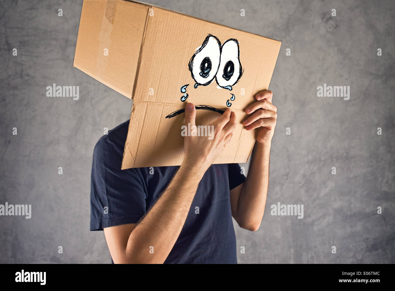 Man with cardboard box on his head and sad crying face expression. Concept of sadness and depression. Stock Photo