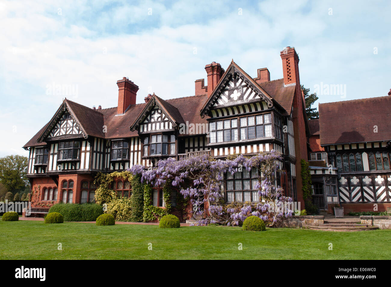 View of the National Trust-owned Wightwick Manor, in Wolverhampton, with beautiful flowering wisteria covering the West wing - Stock Image