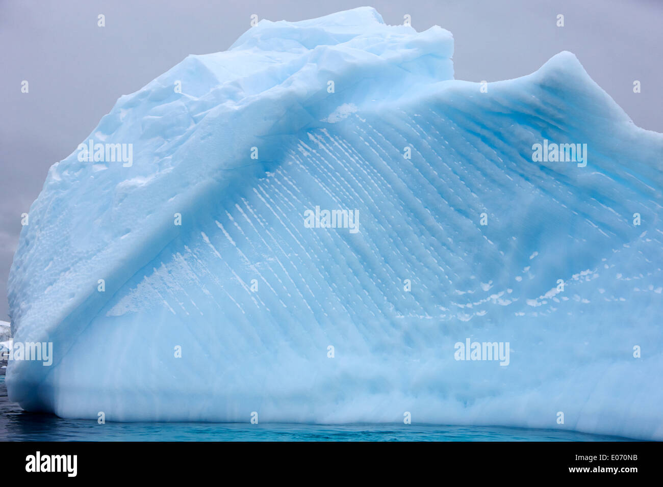 iceberg showing straight striped lines and water line erosion near cuverville island Antarctica - Stock Image