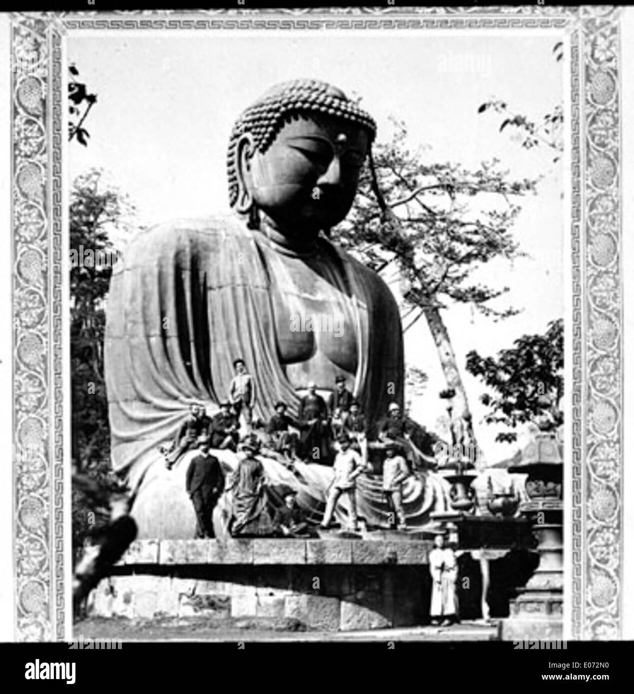 Groupe de voyageurs occidentaux posant aux pieds d'une statue géante de Bouddha, Asie - Stock Image