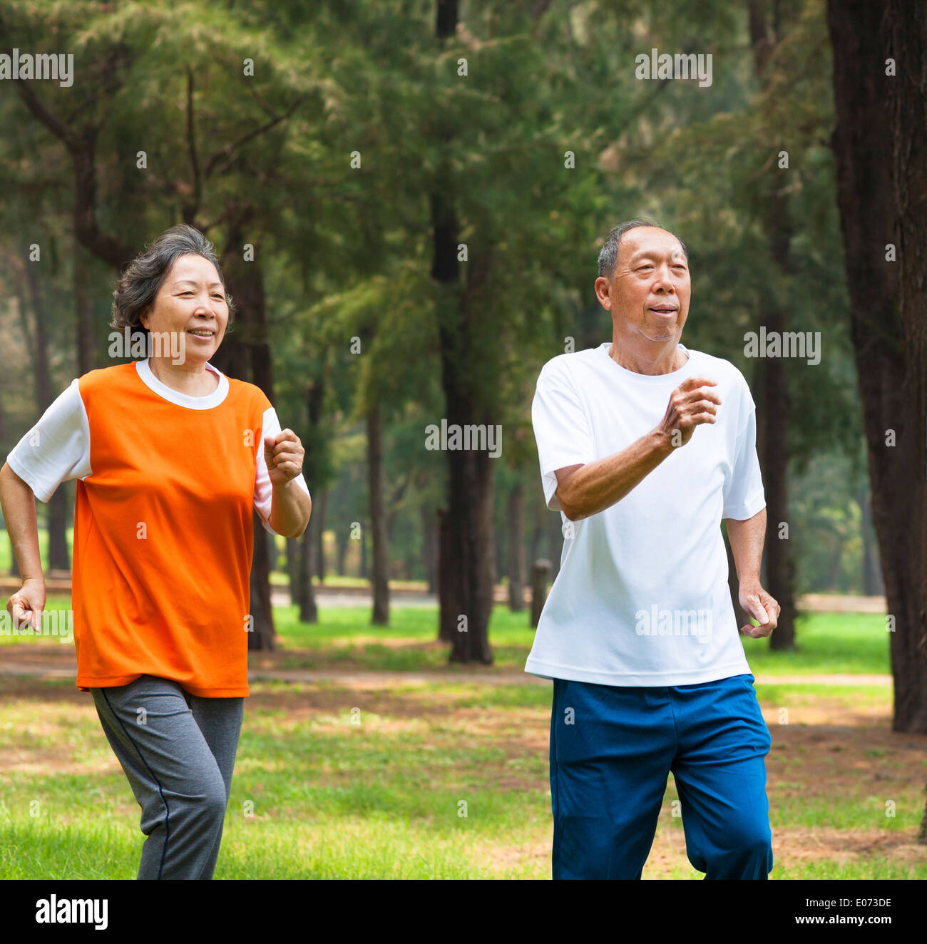 happy senior couple jogging together in the park Stock Photo