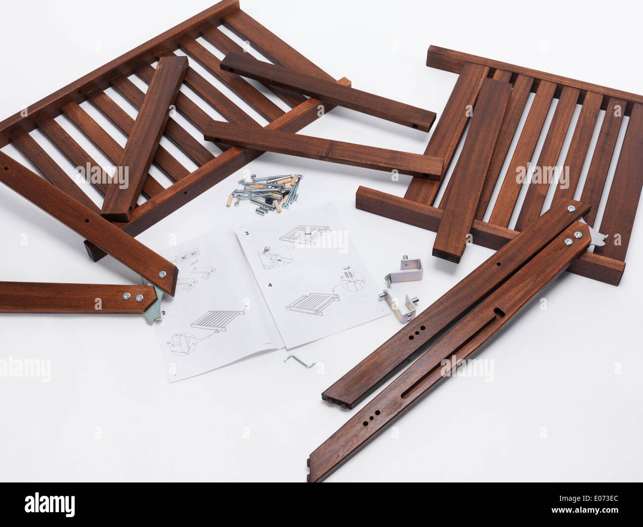 Assembling IKEA furniture parts with instructions - Stock Image