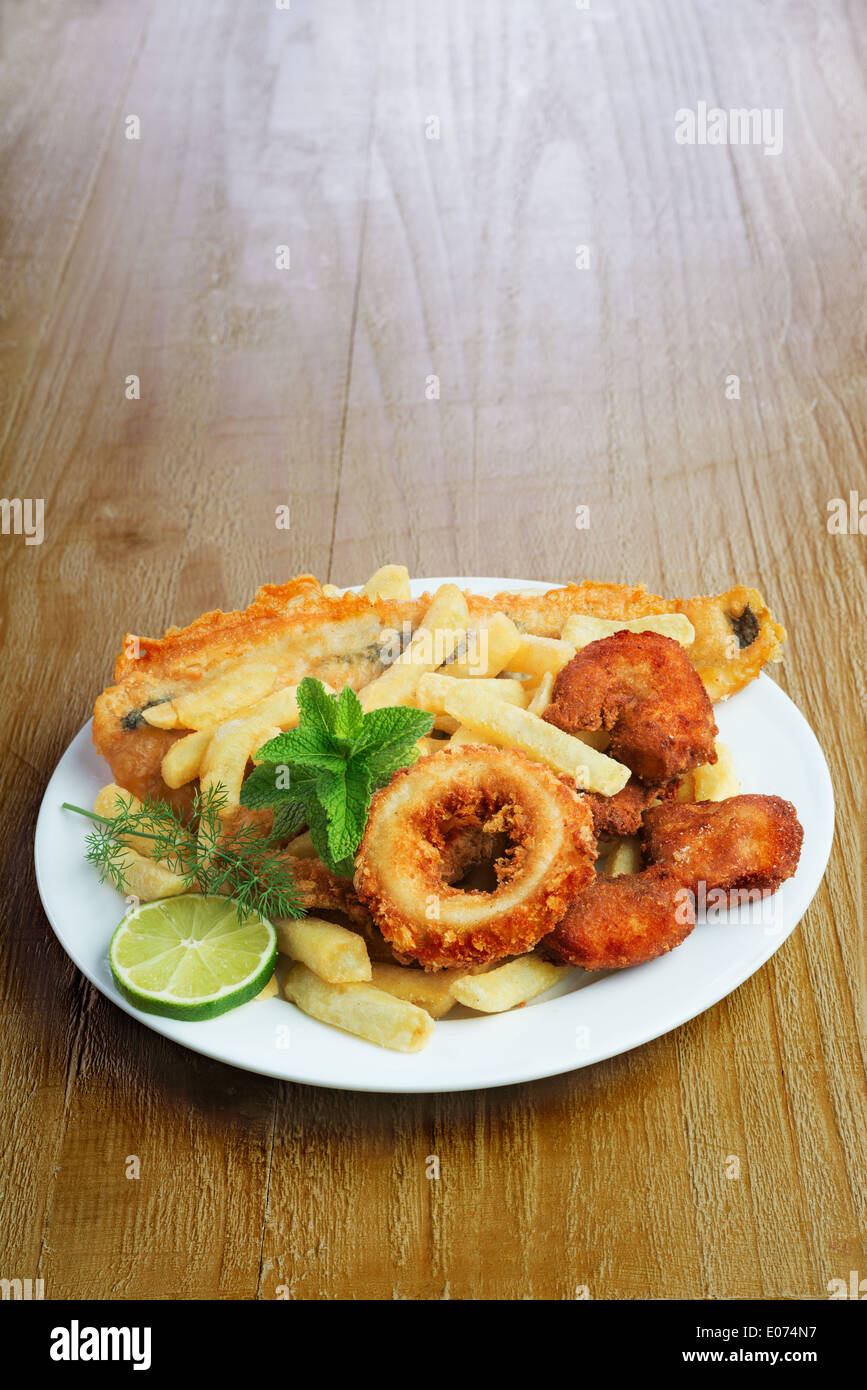 Seafood dish with crumbed fish,calamari,prawn and potato chips on vintage table - Stock Image