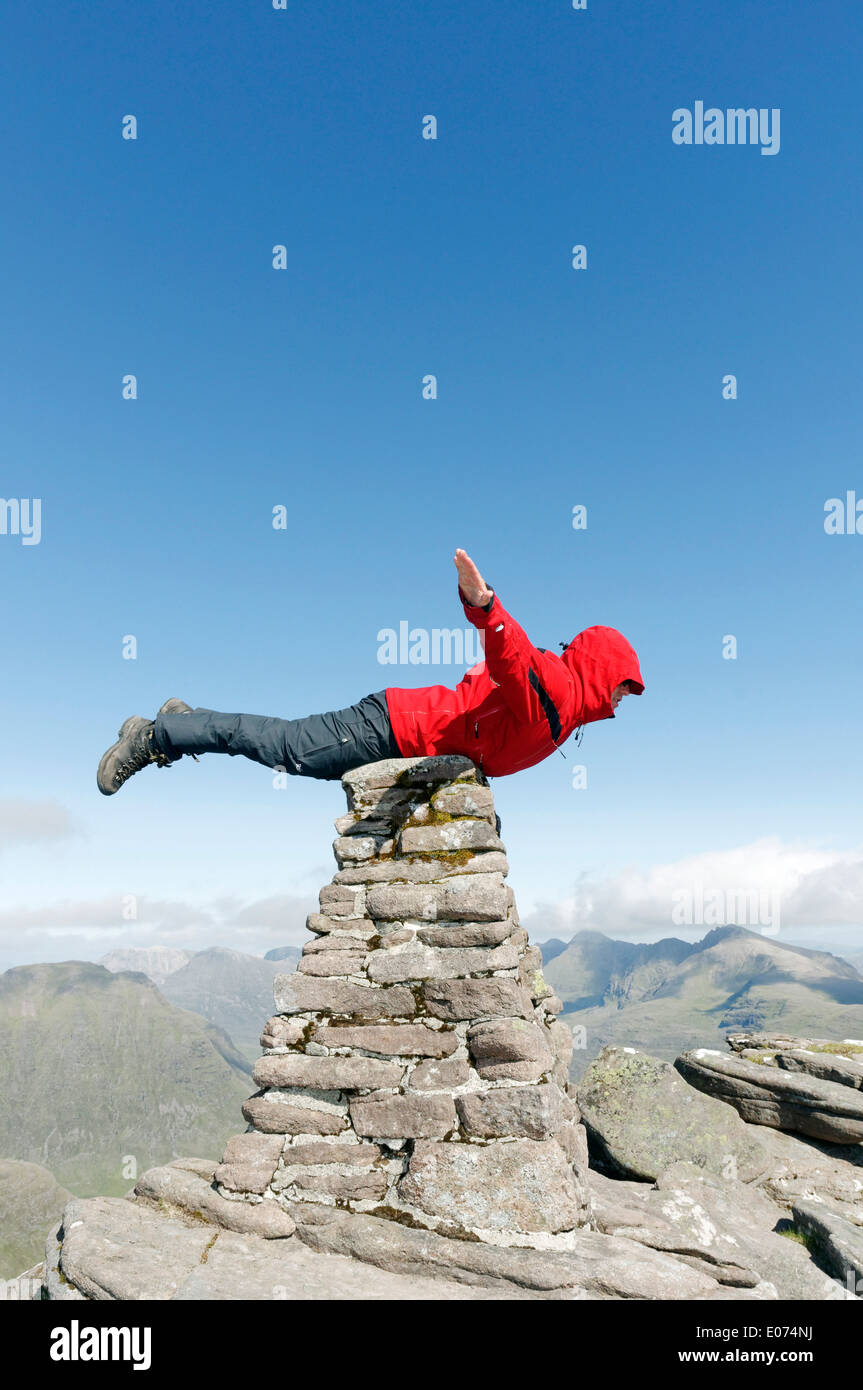 Superman flying stock photos superman flying stock images alamy a hillwalker in a red jacket pretending to be superman flying on the summit cairn publicscrutiny Gallery