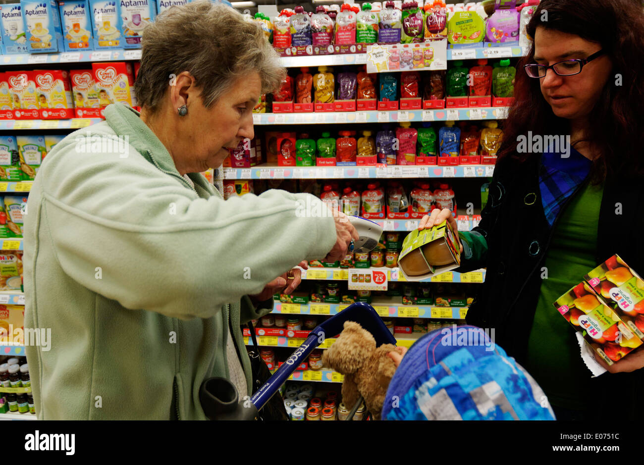 Two women scanning their shopping using Scan as you Shop in Tesco supermarket - Stock Image