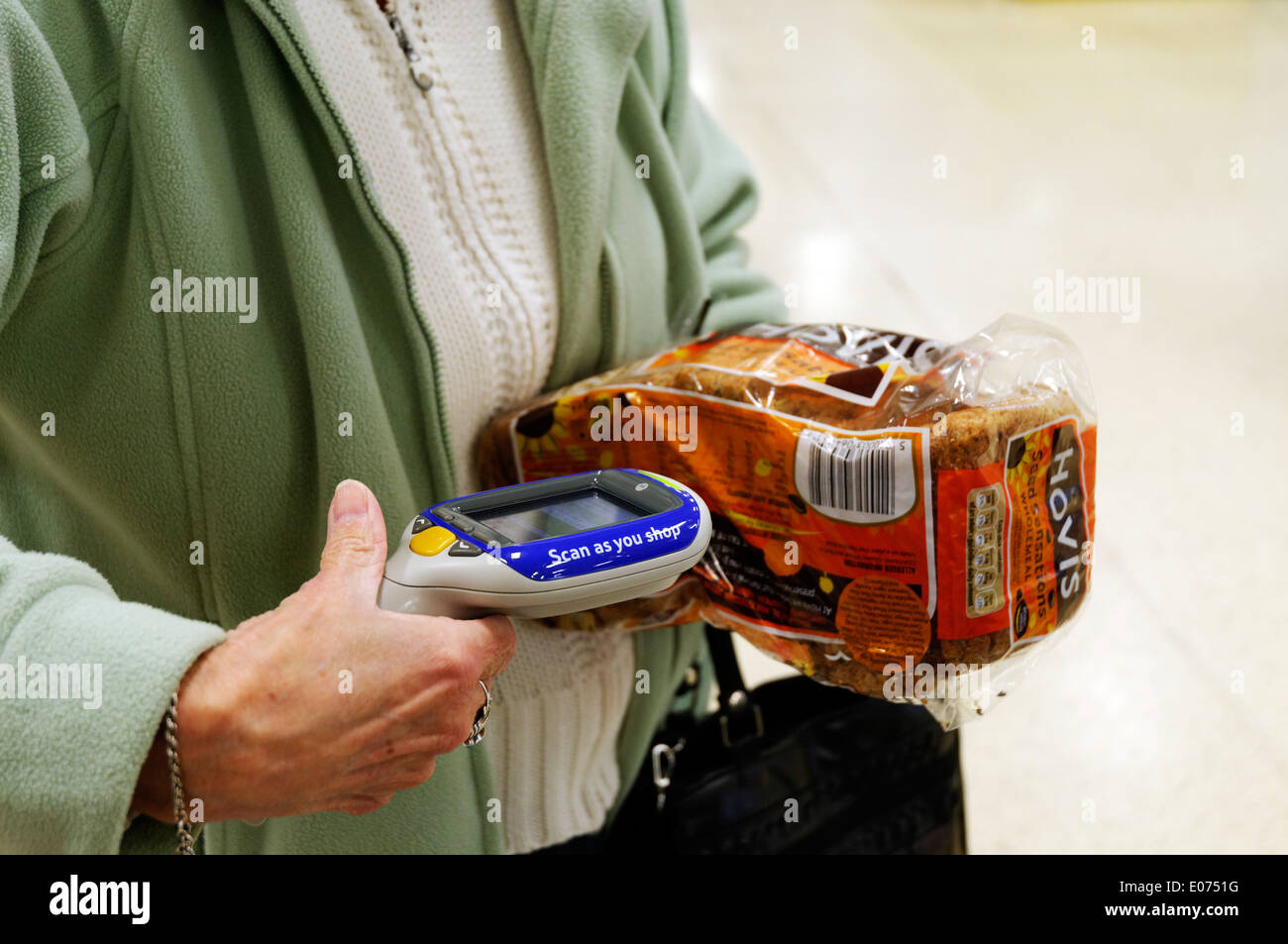 An older woman's hands scanning a loaf of bread in Tesco Scan as you Shop - Stock Image
