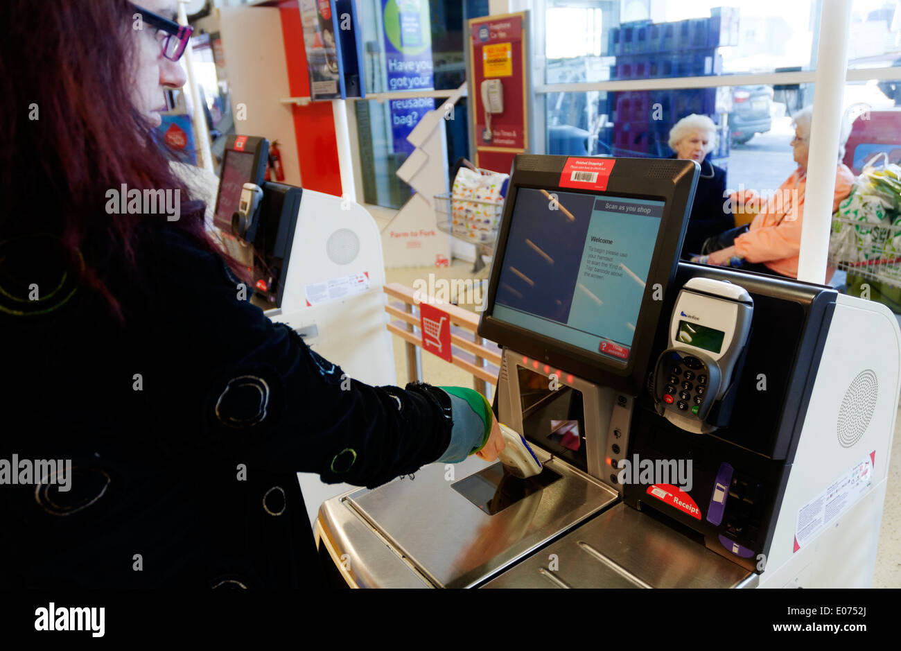 A young woman using the Scan as you Shop till in Tesco supermarket - Stock Image