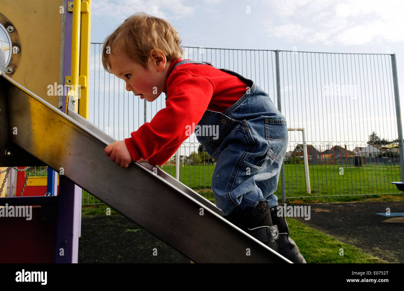 A two year old boy playing on a slide in a playground - Stock Image