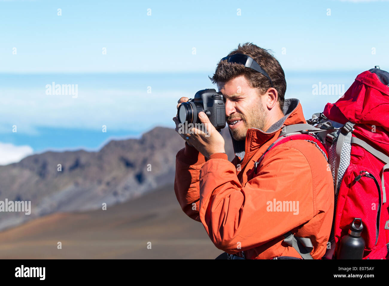 Nature photographer taking pictures outdoors on hiking trip in the mountains - Stock Image