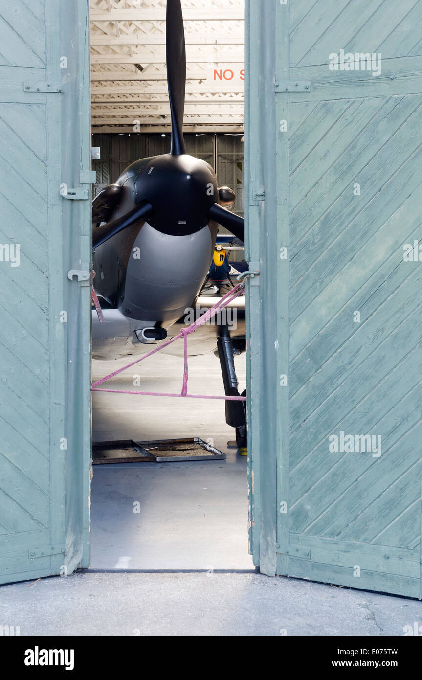 A Supermarine Spitfire fighter plane inside partially opened hangar doors in the restoration shop at Duxford Air Stock Photo
