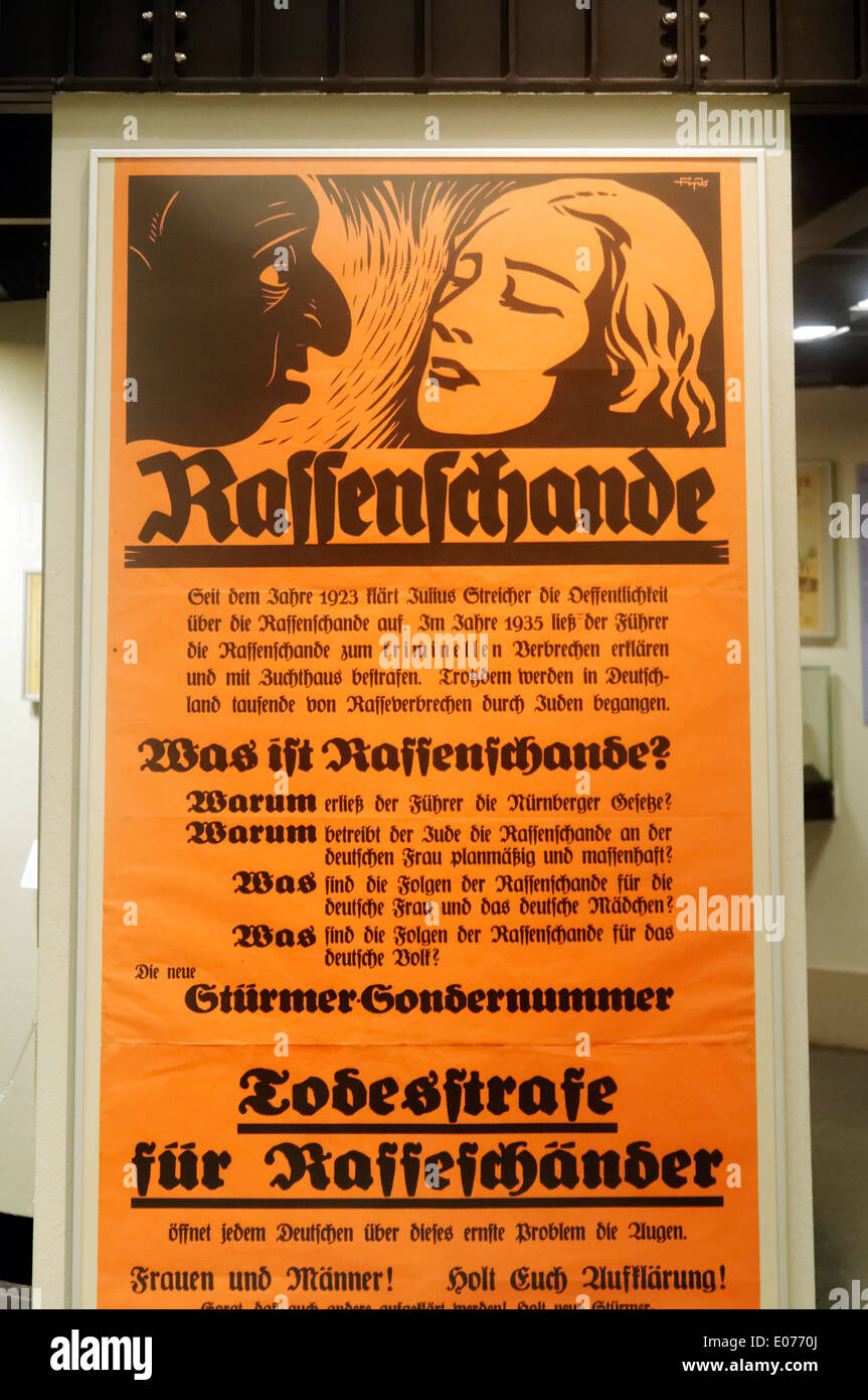 A nazi era poster showing the outline of a jew looking with lust at a blonde with the word 'Rassenschande' or 'Racial Defilement - Stock Image