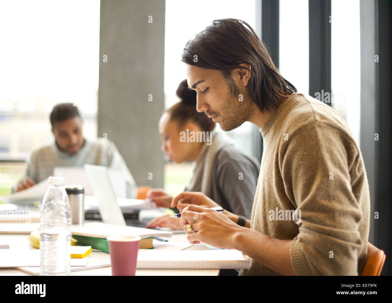 Young man talking notes for study with students studying in background. University students preparing for final exams in library - Stock Image