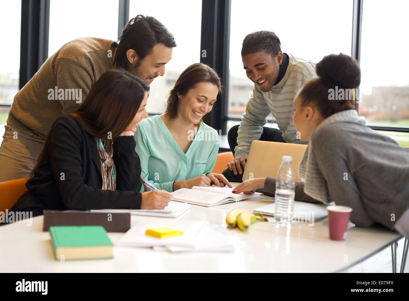 Group of happy young students in cooperation with their school assignment. Multiethnic young people sitting at table reading. - Stock Image