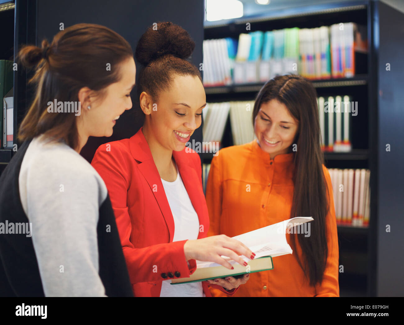 Diverse group of college students in library reading a book together. Female students looking for information in reference books - Stock Image