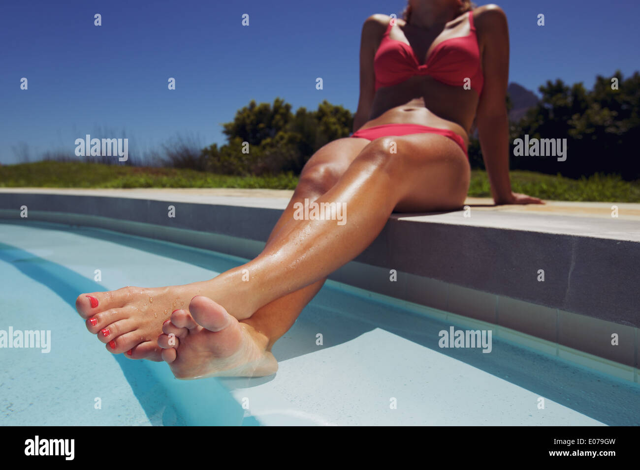 Low angle view of female model relaxing by the pool with her legs in water. Young woman in bikini sunbathing by Stock Photo