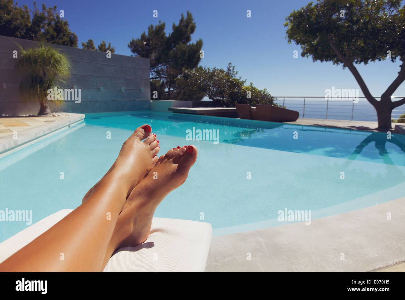 Bare feet of young lady lying on deck chair sunbathing by the swimming pool. - Stock Image