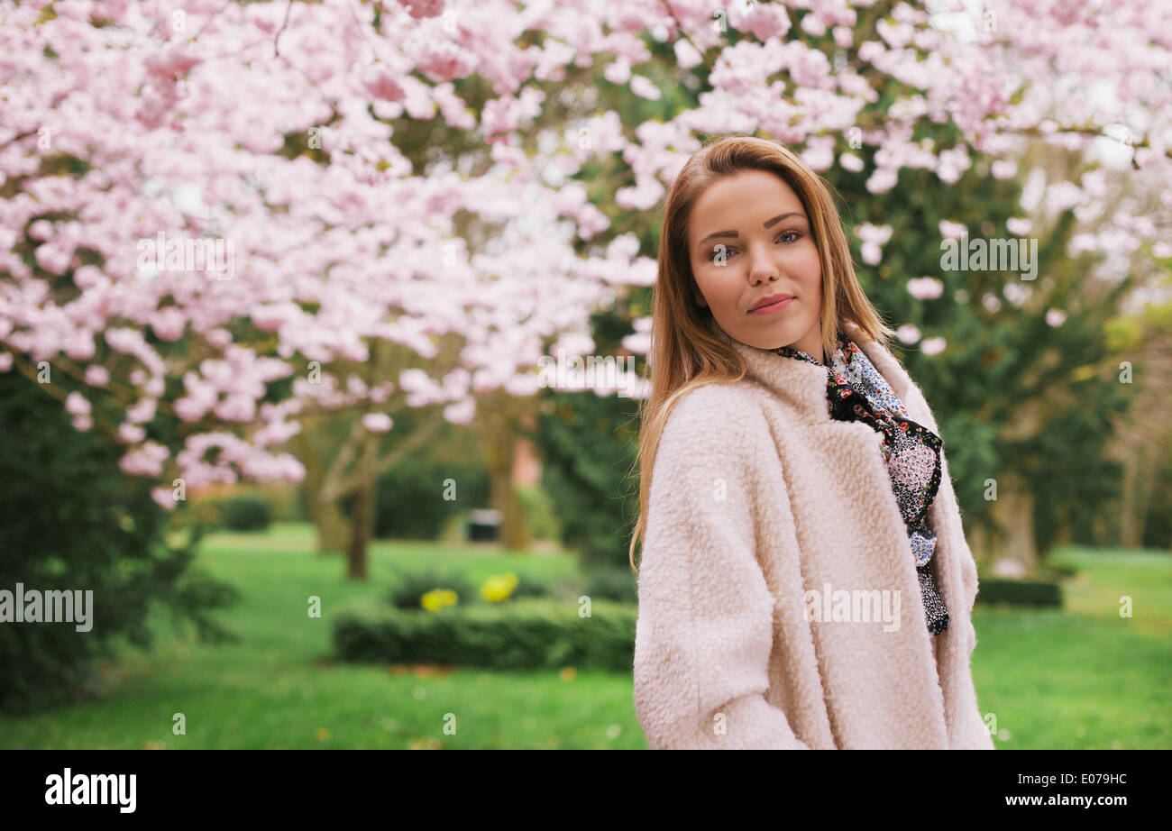 Portrait of beautiful young woman posing at the spring blossom garden. Attractive caucasian female model outdoors Stock Photo