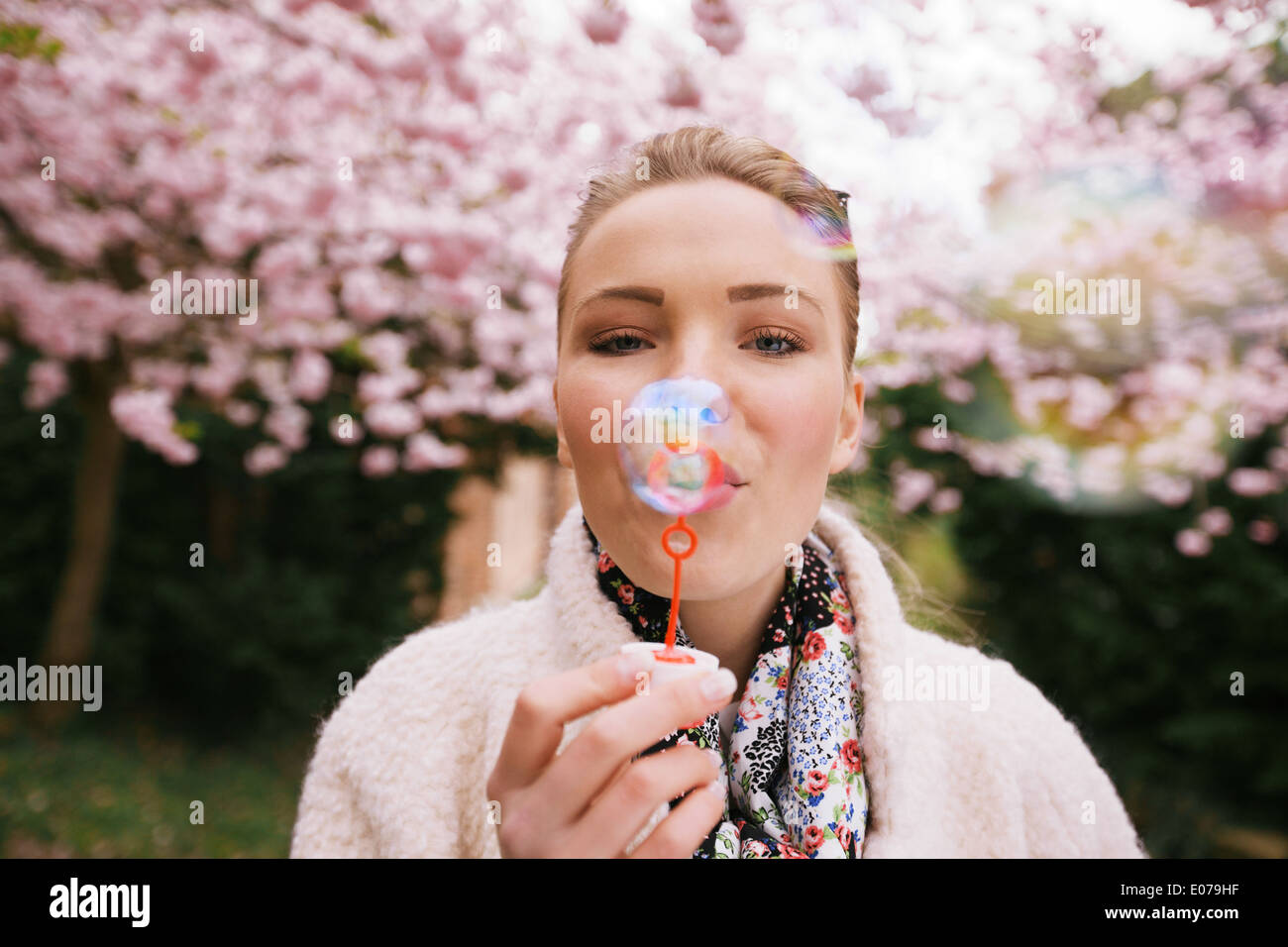 Portrait of beautiful young woman blowing bubbles at park. Pretty female model with bubble wand at spring blossom garden. - Stock Image