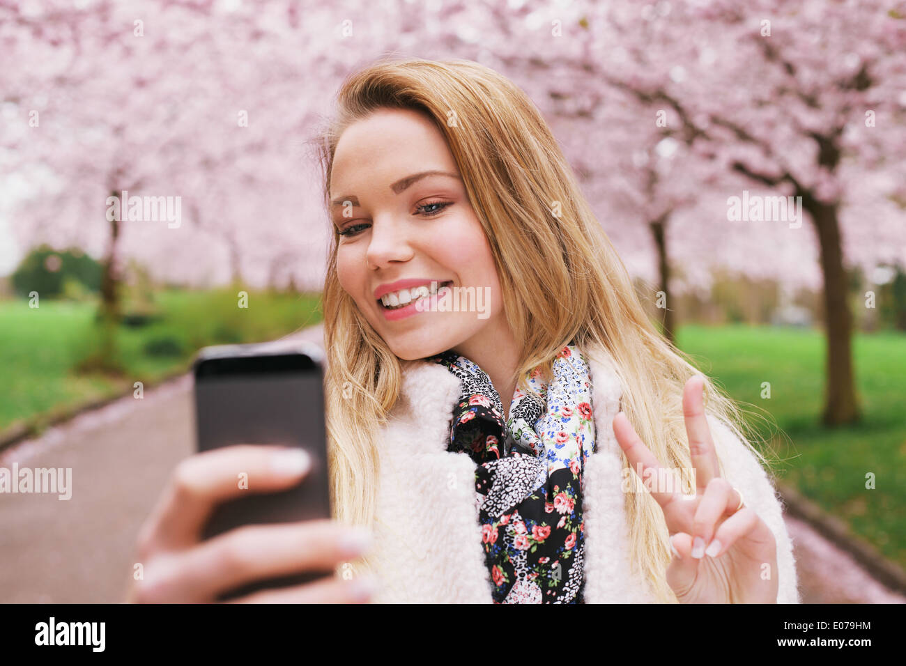 Pretty young female model gesturing peace sign while taking her picture with cell phone. Beautiful caucasian young woman. - Stock Image